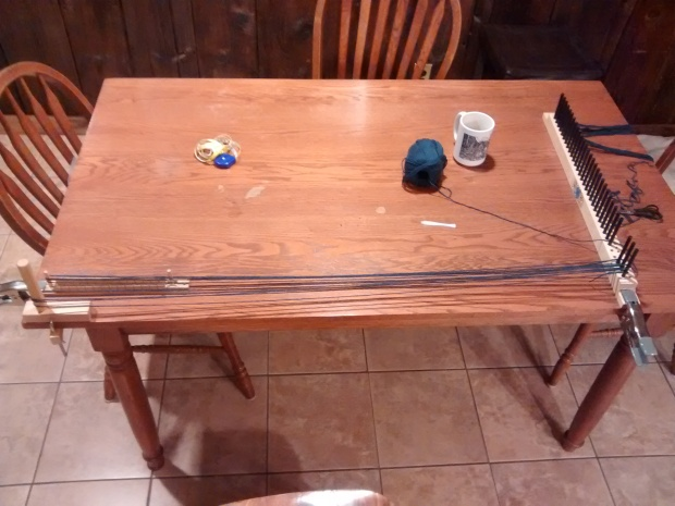 A picture of my warping process, using the peg loom itself, a warping peg, and a pompon rug loom on my kitchen table.